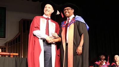Charles Sturt Provost and DVC Academic Professor John Germov congratulates Dr James Mwendwa
