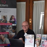Associate Professor Rev'd Andrew Cameron manning the stall for St Marks National Theological Centre, CSU, Canberra. Photograph by Sarah Stitt