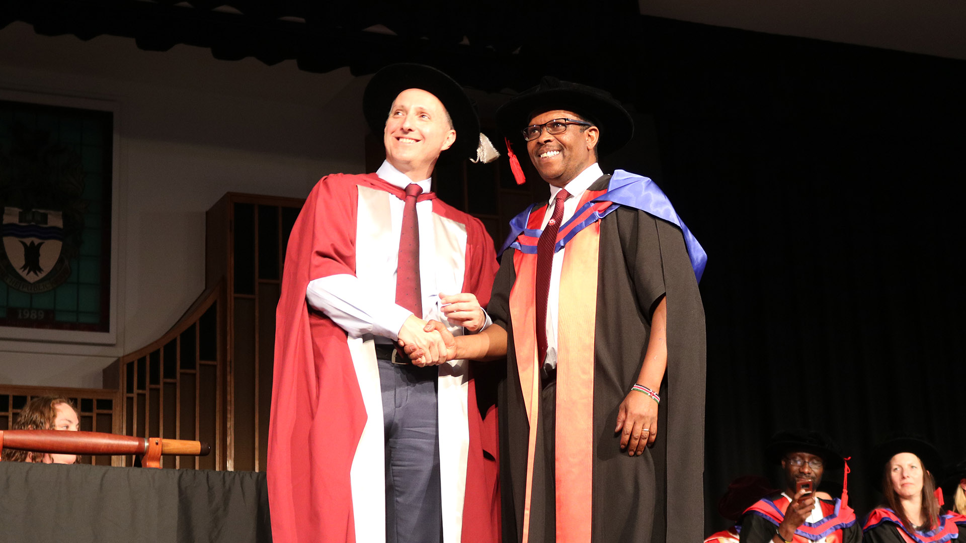 Provost and DVC Academic Professor John Germov presents Dr Mwendwa with his PhD