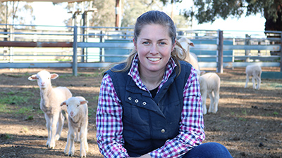 PhD student Kayla Kopp with lambs