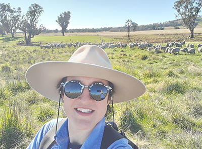 PhD student Amy Bates in front os sheep