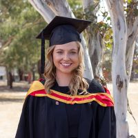 Woman in her full graduation gown smiling in front of a gum tree.