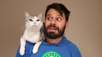 a photo of a man with a cat on his shoulder