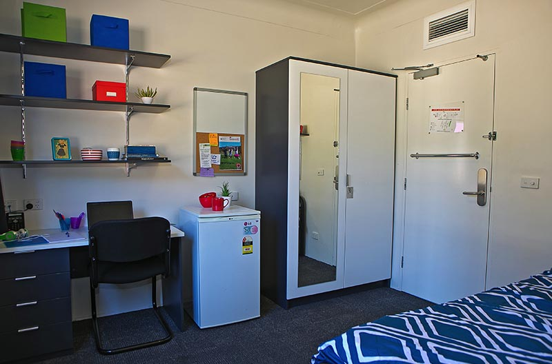 A wide view of a room showing study area and wardrobe storage