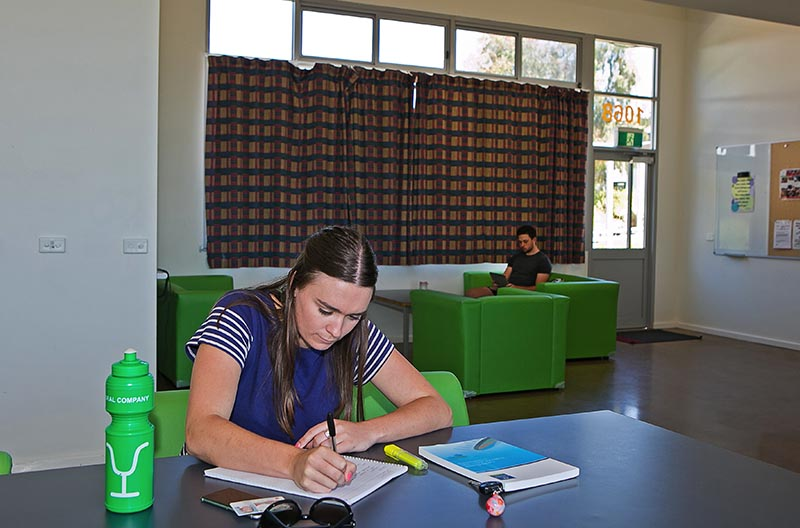 Two students studying and relaxing in the common area